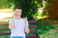 一件白色T恤杉的一个年轻欧洲人在电话里说并且坐一条长凳在城市公园 人看他的手指, pu 图库摄影