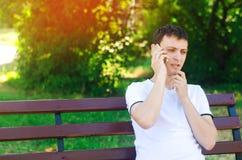 一件白色T恤杉的一个年轻欧洲人在电话里说并且坐一条长凳在城市公园 解决问题的概念, 库存照片