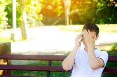 一件白色T恤杉的一个年轻沉思欧洲人在电话里说并且坐一条长凳在城市公园 用他的盖他的面孔 免版税库存图片