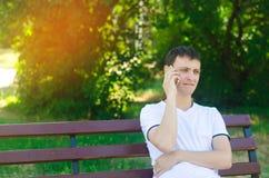 一件白色T恤杉的一个年轻沉思欧洲人在电话里说并且坐一条长凳在城市公园 解决p的概念 库存图片