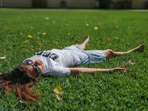 一件白色T恤杉的一美丽的少女有题字断裂的树和裙子在草说谎 免版税库存图片
