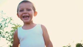 一件白色T恤杉的四岁的男孩笑,孩子跳并且显示在他的手指的类 快乐的激活的画象 股票录像