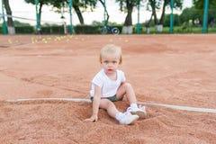 一件白色T恤杉的小逗人喜爱的女孩在网球场坐 微笑的逗人喜爱的孩子画象  免版税库存图片