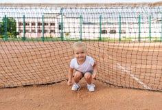 一件白色T恤杉的小逗人喜爱的女孩在网球场 微笑的逗人喜爱的孩子画象  库存图片