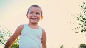 一件白色T恤杉笑的,盖子四岁的男孩他的面孔用他的手,孩子跳反对天空 a纵向 股票录像