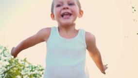一件白色T恤杉笑的,盖子四岁的男孩他的面孔用他的手,孩子跳反对天空 a纵向 股票视频