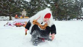 一件皮大衣和一条围巾的一个小女孩在与一束的俄国样式百吉卷在她的脖子上淋浴与雪 股票录像