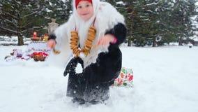 一件皮大衣和一条围巾的一个小女孩在与一束的俄国样式百吉卷在她的脖子上淋浴与雪 股票视频
