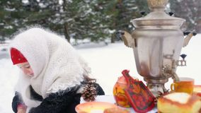 一件皮大衣和一条围巾的一个小女孩在俄国样式坐在一张欢乐桌上并且播放俄国matryoshka 股票视频