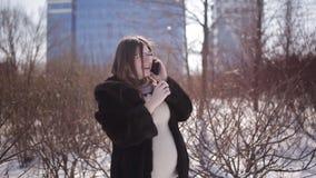 一件皮大衣的怀孕的女孩在冬天谈话在街道的电话 影视素材