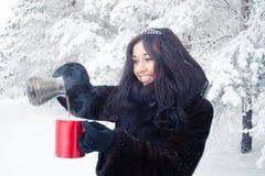 一件皮大衣的美丽的深色的女孩在冬天森林的背景,倒从土耳其人的热的咖啡红色杯的 免版税图库摄影