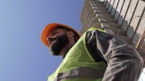 一件盔甲的建筑工头在一座高层建筑物的工地工作附近 4 K 股票录像