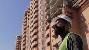 一件盔甲的建筑工头在一座高层建筑物的工地工作附近 4 K 影视素材