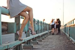 一件短的礼服和鞋子的女孩坐桥梁 妒嫉、闲话、妇女` s问题或者假日的概念 图库摄影