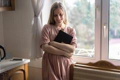一件礼服的一名妇女有长发的在她手和微笑上站立在窗口并且拿着一本书 免版税图库摄影