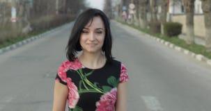 一件礼服的可爱的年轻女人有花的转向照相机和微笑 股票录像