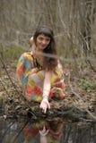 一件礼服的女孩在一个密集的森林里 免版税库存照片