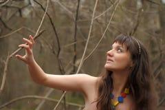 一件礼服的女孩在一个密集的森林里 免版税库存图片