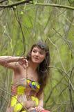一件礼服的女孩在一个密集的森林里 库存照片