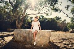 一件礼服的女孩在一块大石头 旅行,假期 突尼斯 库存图片