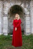 一件礼服的妇女在城堡旁边 图库摄影