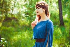 一件礼服的妇女在森林 库存照片