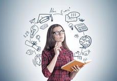 一件礼服的少妇有书的,教育 免版税库存照片