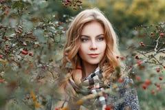 一件秋季典雅的外套的美丽的俏丽的欧洲年轻女人在葡萄酒方格的米黄围巾放松户外 免版税图库摄影