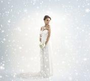 一件空白礼服的一个新娘在一个多雪的背景 免版税库存图片