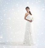 一件空白礼服的一个新娘在一个多雪的背景 库存图片
