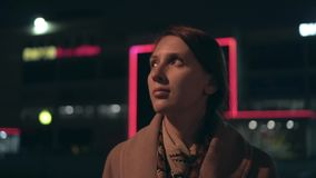 一件米黄外套的疲乏的女孩有被撕碎的头发的走在一条黑暗的街道上的在工作以后 股票视频