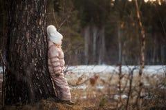 一件米黄夹克和一个白色帽子的走在领域的一个女孩的秋天画象 库存照片