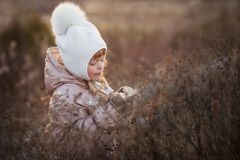 一件米黄夹克和一个白色帽子的走在领域的一个女孩的秋天画象 库存图片