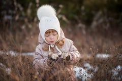 一件米黄夹克和一个白色帽子的走在领域的一个女孩的秋天画象 免版税库存照片