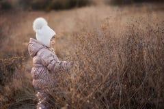 一件米黄夹克和一个白色帽子的走在领域的一个女孩的秋天画象 免版税库存图片