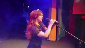 一件精采黑礼服的一位年轻棕色毛发的女演员在一阵烟幕的阶段唱歌 股票录像