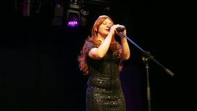 一件精采黑礼服的一位年轻棕色毛发的女演员在阶段唱歌在一阵烟幕的话筒 影视素材