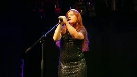 一件精采黑礼服的一位年轻棕色毛发的女演员在阶段唱歌在一阵烟幕的话筒 股票录像
