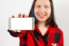 一件红色和黑衬衣的一名少女妇女拿着有一个空白的白色屏幕的一个智能手机水平地在她前面 库存照片