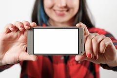 一件红色和黑衬衣的一名少女妇女拿着有一个空白的白色屏幕的一个智能手机水平地在她前面 免版税图库摄影