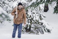 一件红色夹克有草丛的和一条绳索的一个人在冬天森林人收集木柴 免版税库存图片