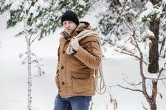 一件红色夹克有草丛的和一条绳索的一个人在冬天森林人收集木柴 库存图片