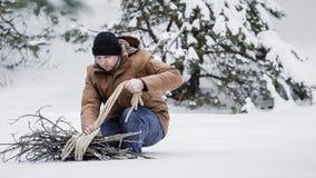 一件红色夹克有草丛的和一条绳索的一个人在冬天森林人收集木柴 免版税库存照片