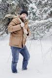 一件红色夹克有草丛的和一条绳索的一个人在冬天森林人收集木柴 免版税图库摄影