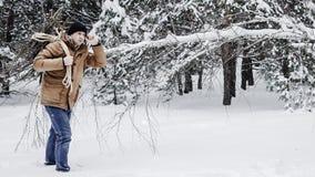 一件红色夹克有草丛的和一条绳索的一个人在冬天森林人收集木柴 图库摄影