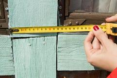 一件红色夹克的一个少妇为建筑和修理工作使用一卷测量的磁带在您的庭院 免版税库存照片