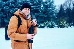 一件红色夹克的一个年轻人有站立在雪和拿着热水瓶和一个杯子茶的背包的 冻森林 图库摄影