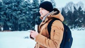 一件红色夹克的一个年轻人有站立在雪和拿着热水瓶和一个杯子茶的背包的 冻森林 免版税库存照片