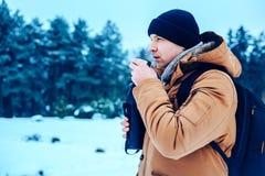 一件红色夹克的一个年轻人有站立在雪和拿着热水瓶和一个杯子茶的背包的 冻森林 库存照片