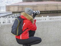 一件红色夹克的女孩摄影师 免版税库存图片